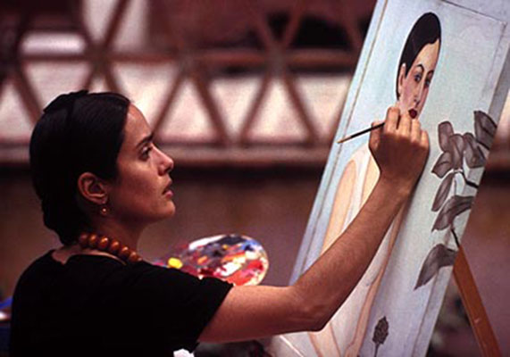 Film still from Hollywood movie Frida: Selma Hayek miming Frida Kahlo painting a self-portrait